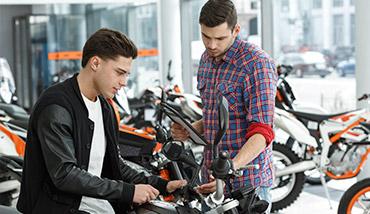 Un chico informándose sobre una moto